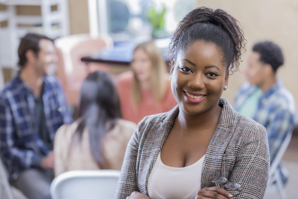 A woman stands confidently in front of her support group. She is smiling at the camera with her arms crossed.