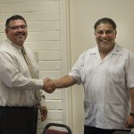 Palomar College Governing Board President John Halcón, right, congratulates the College's incoming Interim Superintendent/President Adrian Gonzales following Gonzales' approval at a special meeting of the Governing Board on June 23. (photo by Melinda Finn)