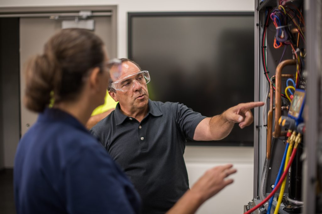 HVAC instructor with student beside air conditioning unit.