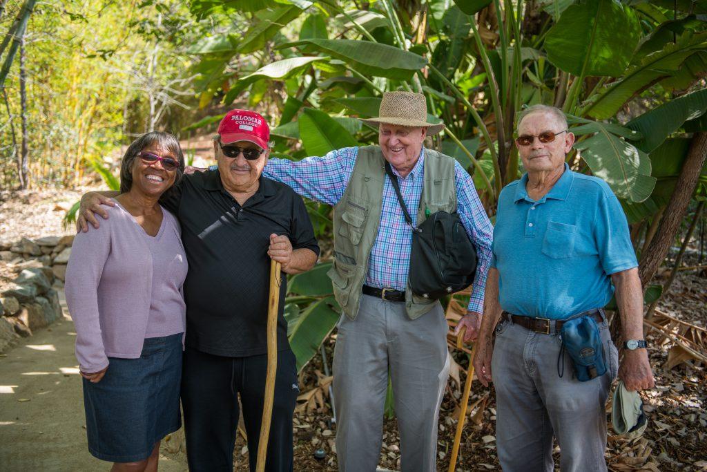 Four people posing in an arboretum