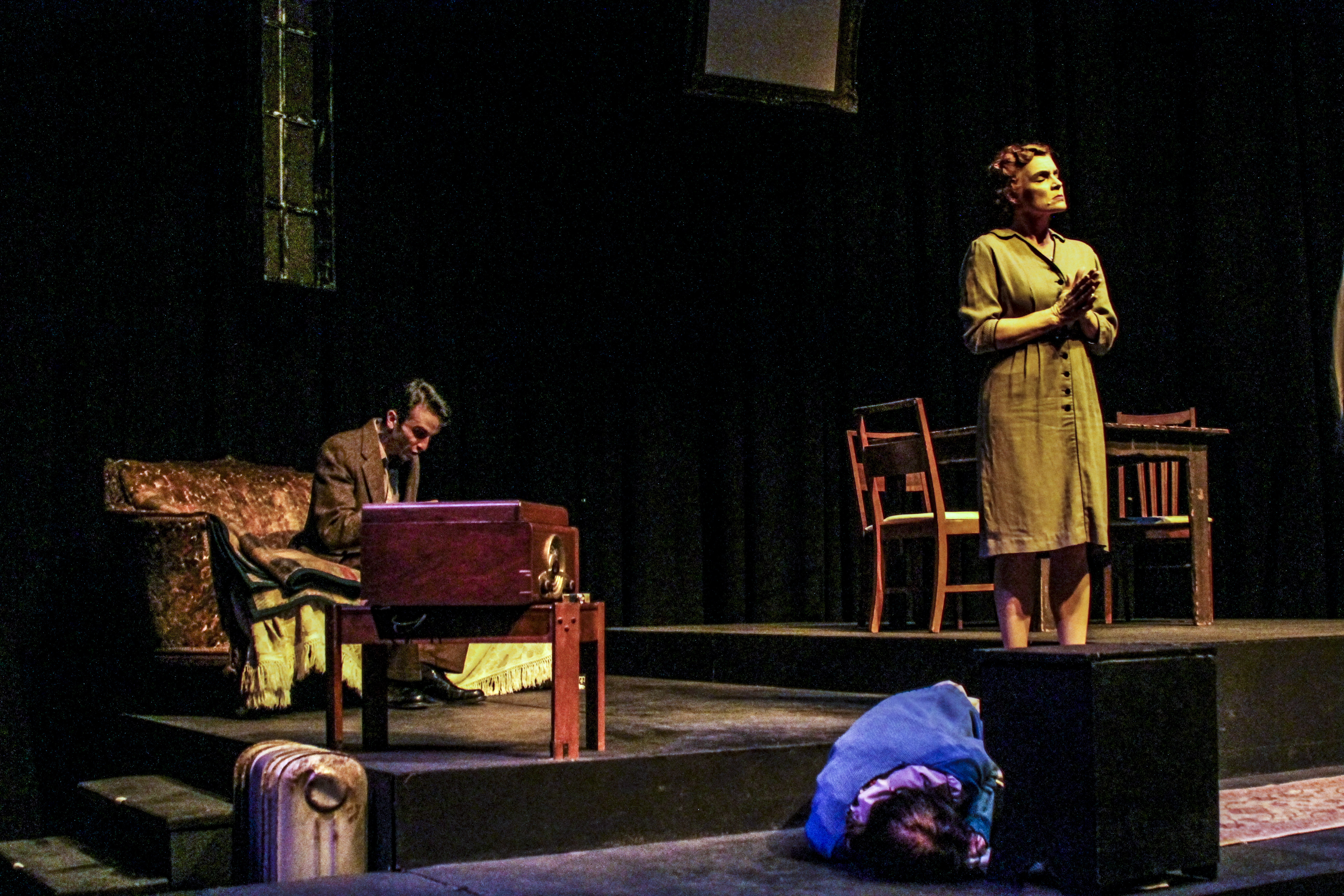 """Laura Wingfield (bottom right, performed by Abby Fields) huddles on the gorund while herover bearing mother Amanda (far right, performed by Heidi Bridges) argues with her son Tom about his nightly escapades to """"the movies,"""" in the performance ofThe Glass Menagerie by Tennessee Williams at Palomar College. Lucas Spenser/Telescope."""