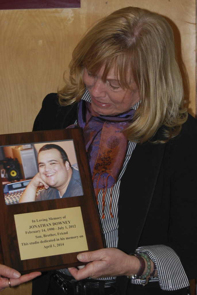 Mary Curran-Downey holds a plague of her deceased son, Jonathan Downey, that will be on display at Palomar College radio station KKSM. Photo Courtesy of Serena Reid