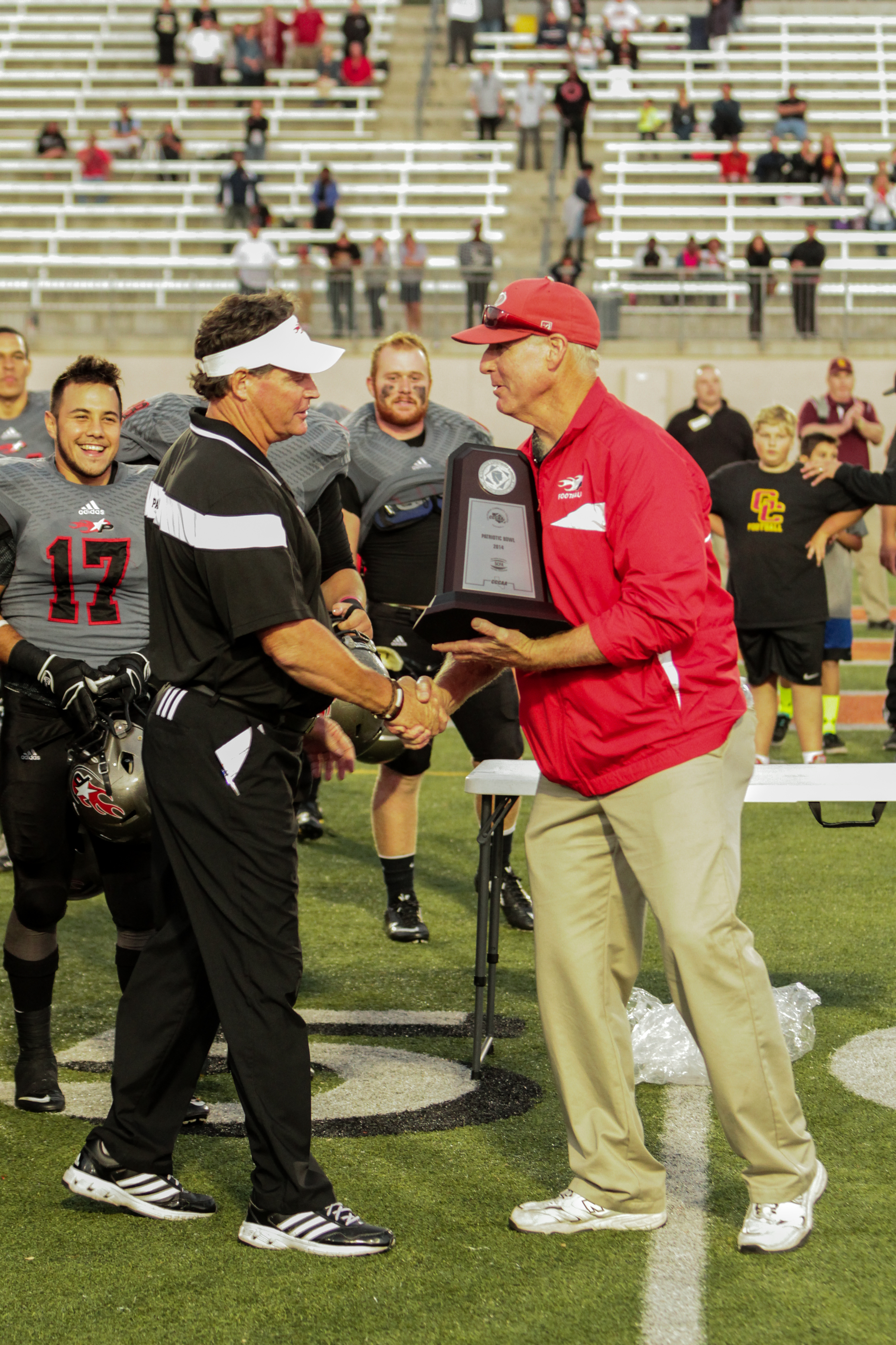November 22, 2014 |Palomar Athletic Director Scott Cathcart presents Palomar Head Football Coach Joe Early with the Patriotic bowl trophy. The Comets defeated the Vaqueros 30-22 and win the Patriotic Bowl at Escondido HS, in Escondido California.| Photo Credit: Philip Farry | The Telescope