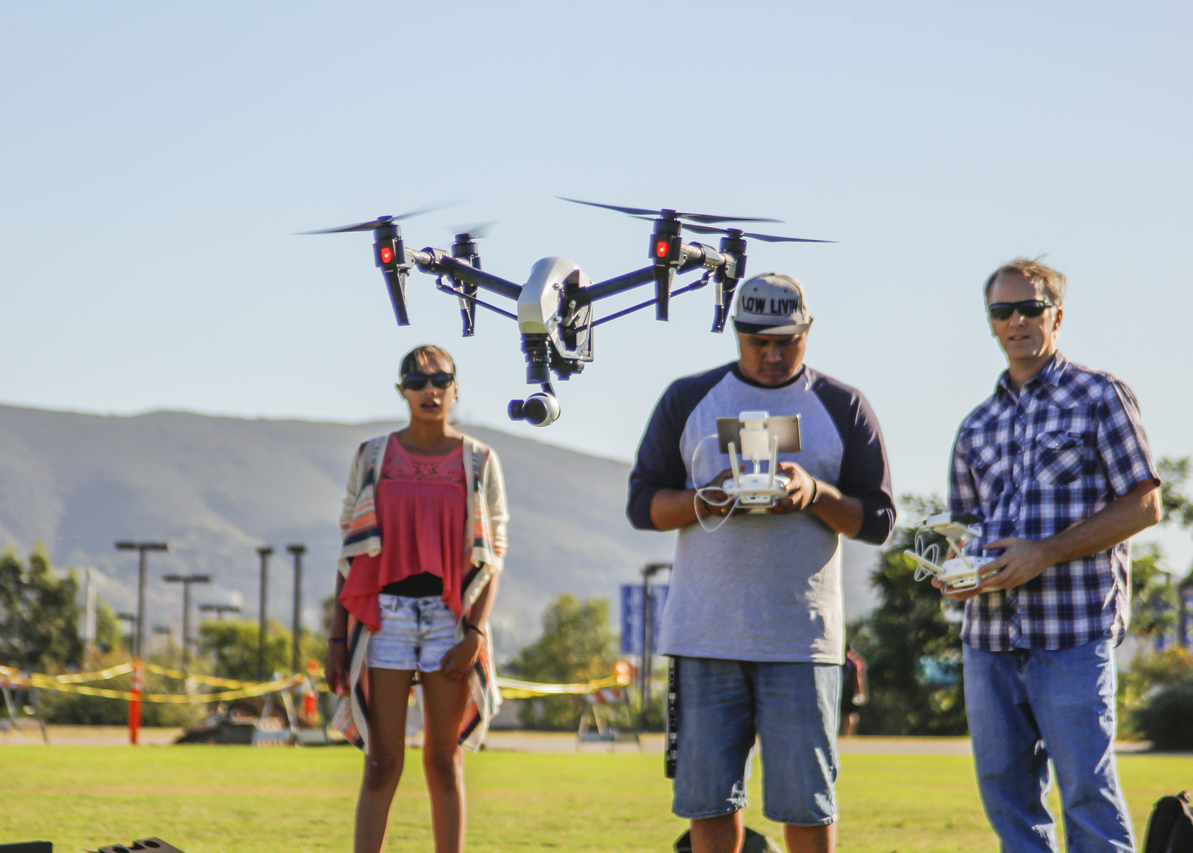 Victor Ramirez (C)is midflight of his U.A.V DJI-S900 along side of Professor Mark Bealo (R) and Michelle Ramierz ( L). Victor Ramirez is one of 22 students in the Digital Imaging with Drones course at the San Marcos campus. September 2015 Hanadi Cackler/ The Telescope