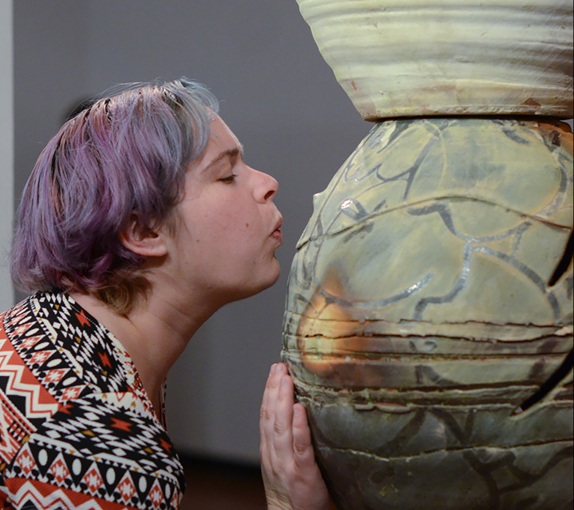 Gallery attendee Michelle Hauswirth blows into ceramic artist Jessica Rae Thompson's sculpture thereby creating a whistle sound during the Ceramics Biennial at the Palomar College Boehm Gallery on Feb. 18. Tracy Grassel/The Telescope