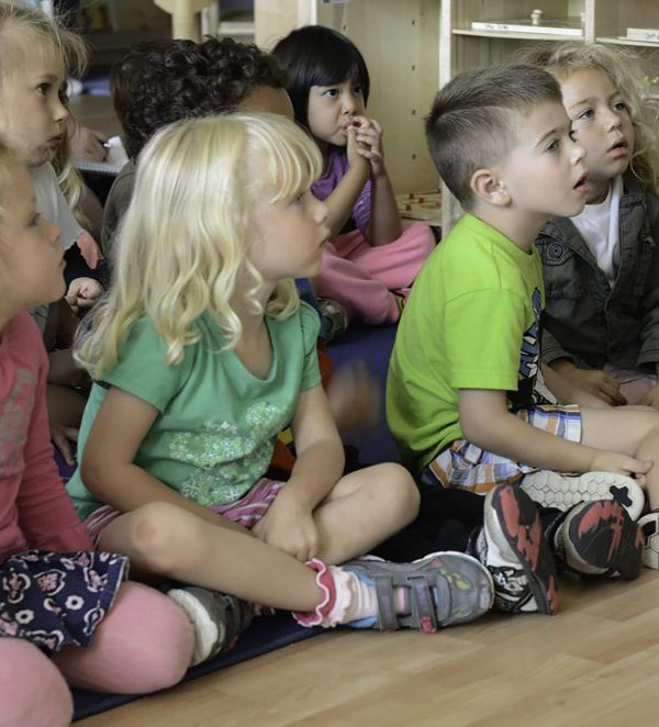 ECE (Early Childhood Education) Classroom 5 children sit and listen to their teacher read them a story before heading outside for recess. Tracy Grassel/The Telescope