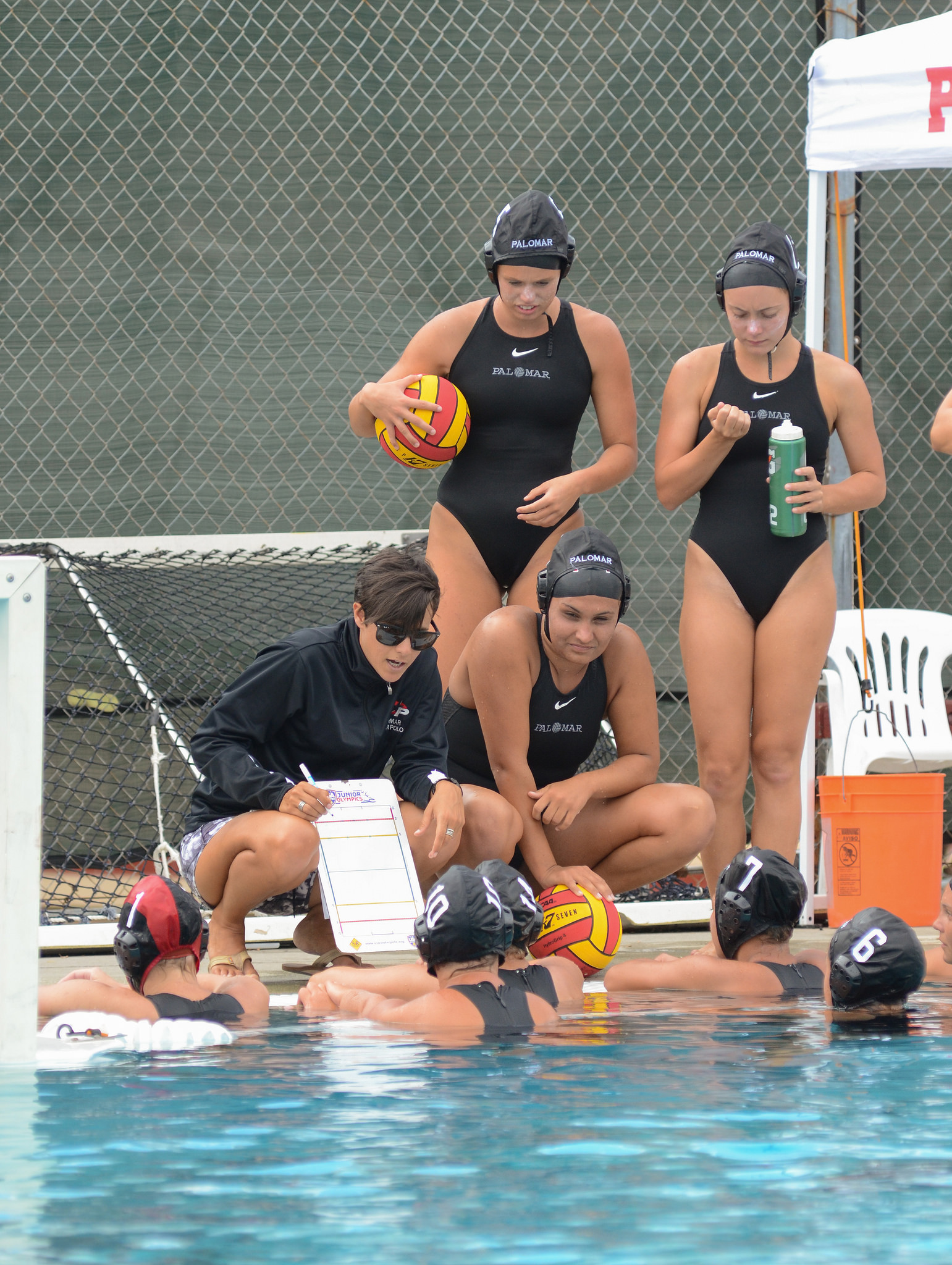 Palomar Head Coach Jackie Puccino dicusses strategic moves with her players during a time-out on Sept. 26. Palomar played Southwestern College at Wallace Memorial Pool and defeated them 19-1. Tracy Grassel/The Telescope