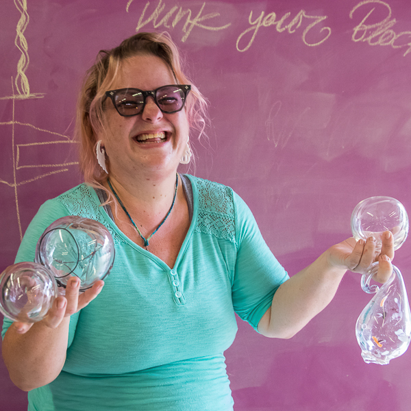 Palomar Student Artist Kris Bandanas proudly poses with some of the blown glass artwork that she has created in her glass blowing class on October 24, 2016. Joe Dusel / The Telescope.