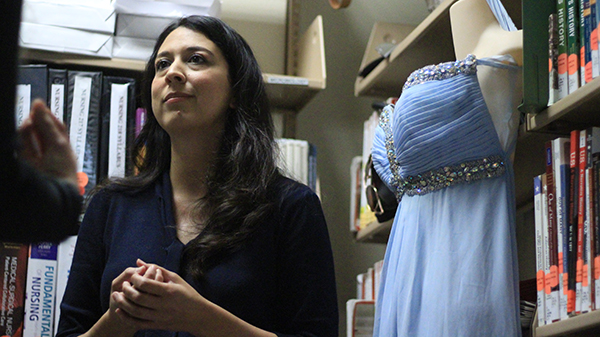 Librarian Natalie Lopez with one of the donated dresses for The Princess Project. Coulter Mohillsmith/The Telescope