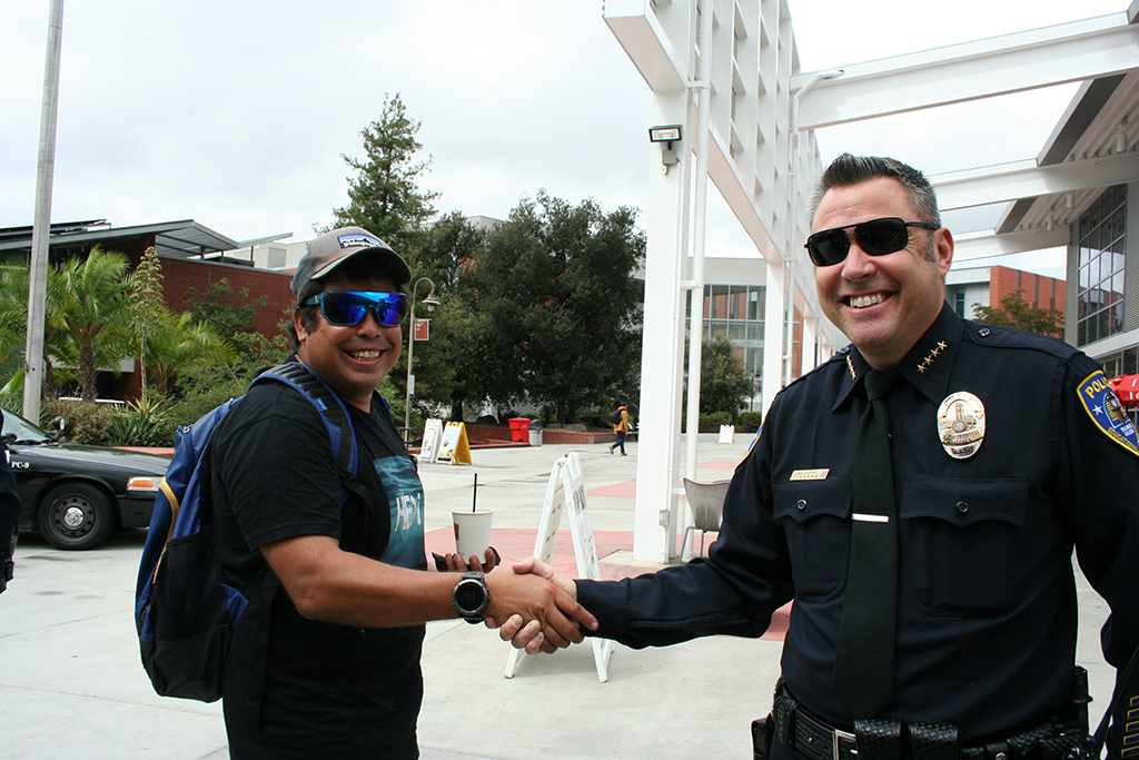 """Palomar College Police Department Chief Chris Moore with student Mike Neill during Coffee With A Cop on Sep 21. Neill stopped by the tables outside the cafeteria to, """"grab a free cup of coffee and thank the officers for all they do"""". Marissa Boyd/The Telescope"""