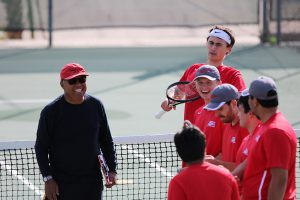 Palomar men's tennis coach Ronnie Mancao jokes with the men's tennis team before a match. April 15. Cameron Niven / The Telescope