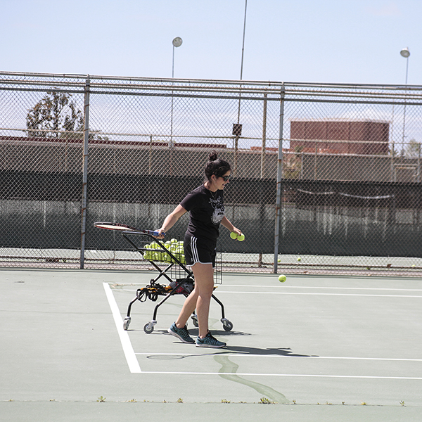 Palomar women's tennis coach Carly de Anda serves to members of the Palomar Comets during practice April 16. Savhanna Vargas/ The Telescope