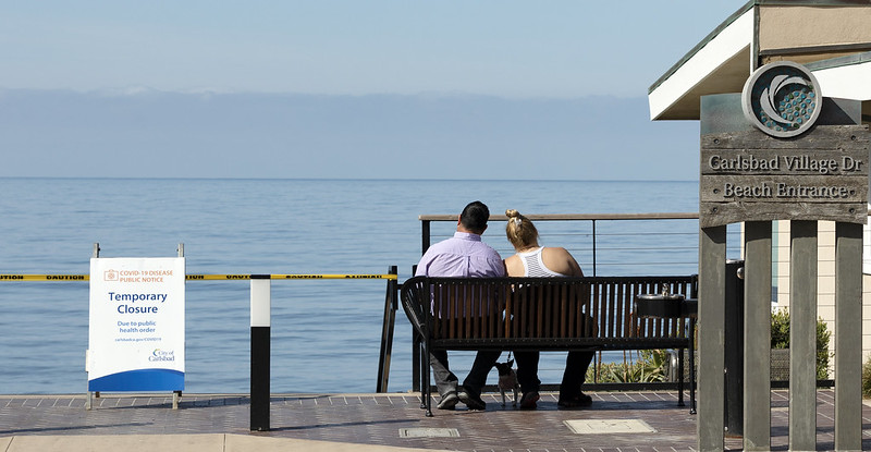 A couple sits on a bench near a closure sign at a Carlsbad beach.