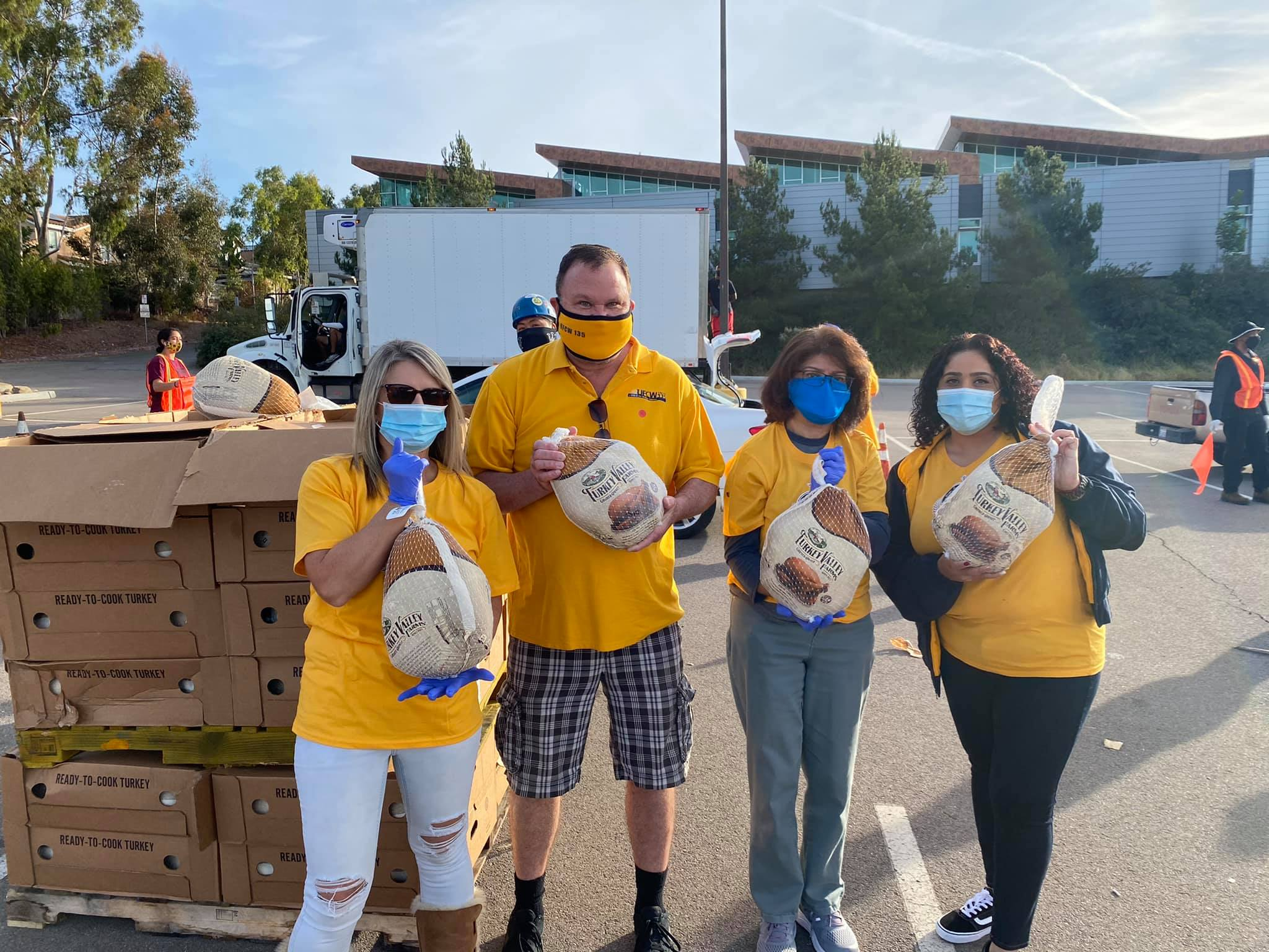 Palomar employees hand out frozen chicken at Palomar food drive in December 2020.